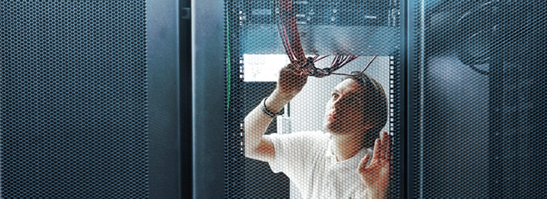 Close-up of an MGB Systems specialist examining wires in the server room of a data center